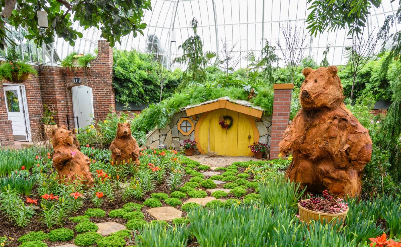 Three topiary bears stand in front of a small cottage in a display in Phipps' South Conservatory during Spring Flower Show.